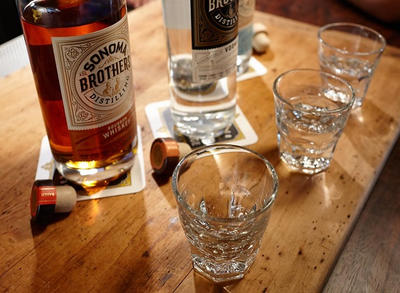 Sonoma Brothers Distilling whiskey and vodka bottles on table with glasses