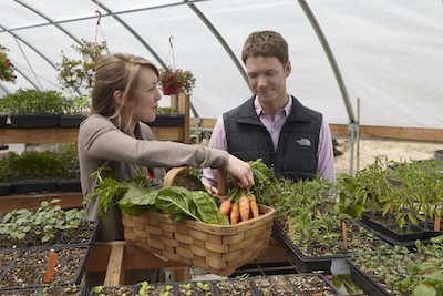 Garrett Martin in greenhouse with Jennifer Harris at Brix farm and vineyard in Healdsburg, California looking over fresh produce