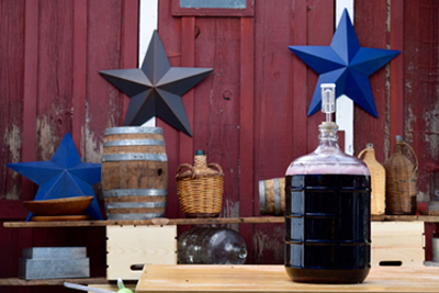 A Carboy with Wine Fermenting in front of a barn.