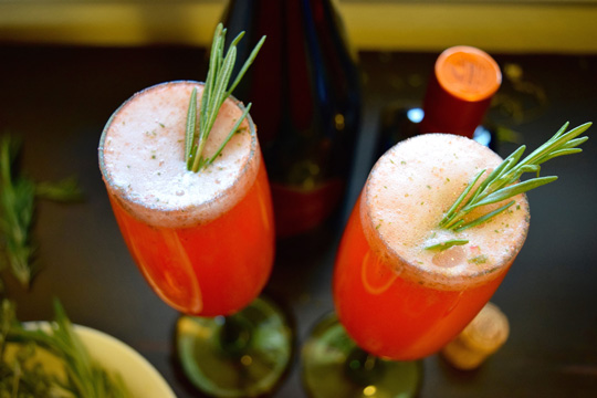 Two champagne glasses with Strawberry cocktail garnished with rosemary
