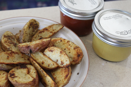 Potato wedges with jars of ketchup and mustard