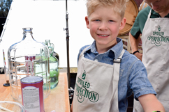 Garrett Martin and son in the Spoiled to Perfection kitchen with carboy and grape juice concentrate